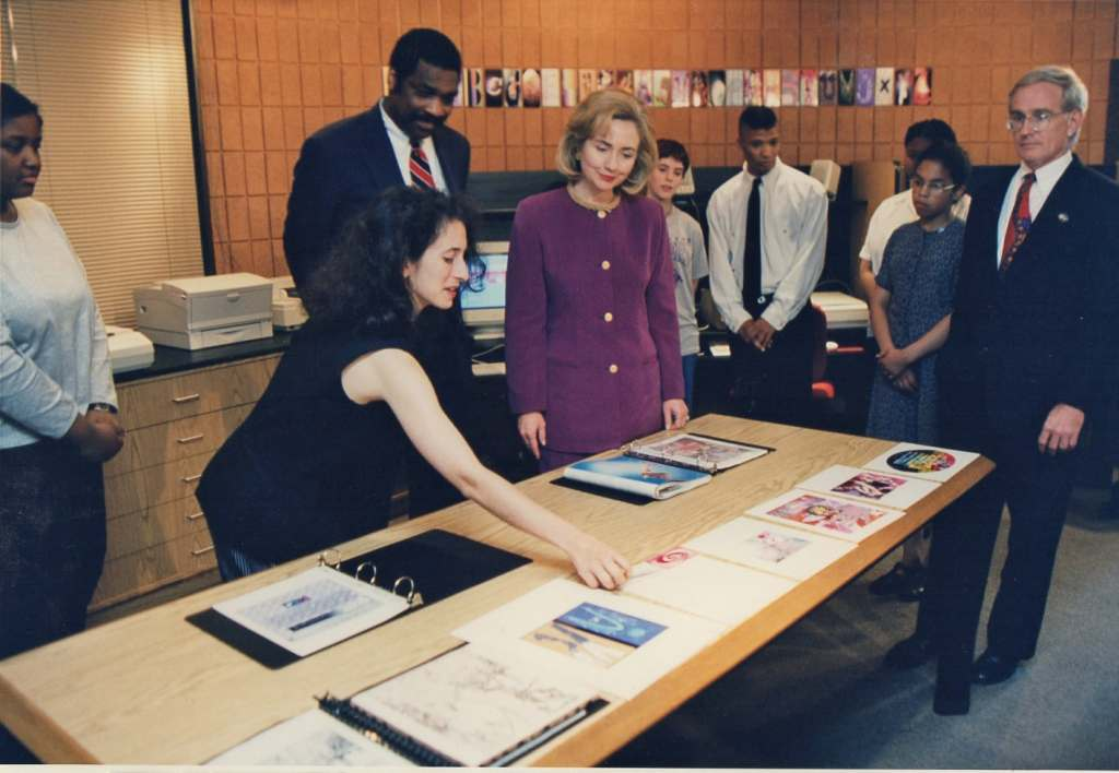Lisa Link shows student art to visiting First Lady Hillary Clinton. Bill Strickland and Pittsburgh mayor and students look.