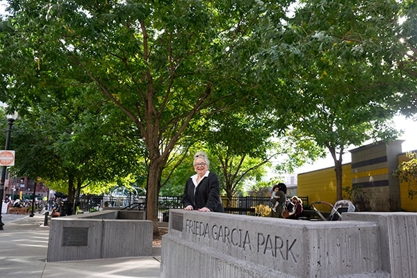 Frieda Garcia in front of park with her name engraved in cement, families at playground in background.